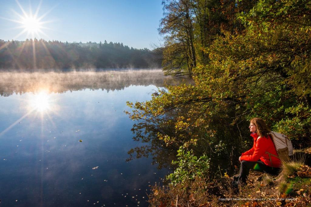 Eine Frau genießt den Sonnenaufgang am Möhnesee. Unmittelbar am Ufer des Vorbeckens Hevesee verläuft die Sauerland-Waldroute. Diese zählt neben dem Rothaarsteig und dem Sauerland-Höhenflig du den drei großen Weitwanderwegen im Sauerland. Mehr Infos unter: www.sauerland-waldroute.de