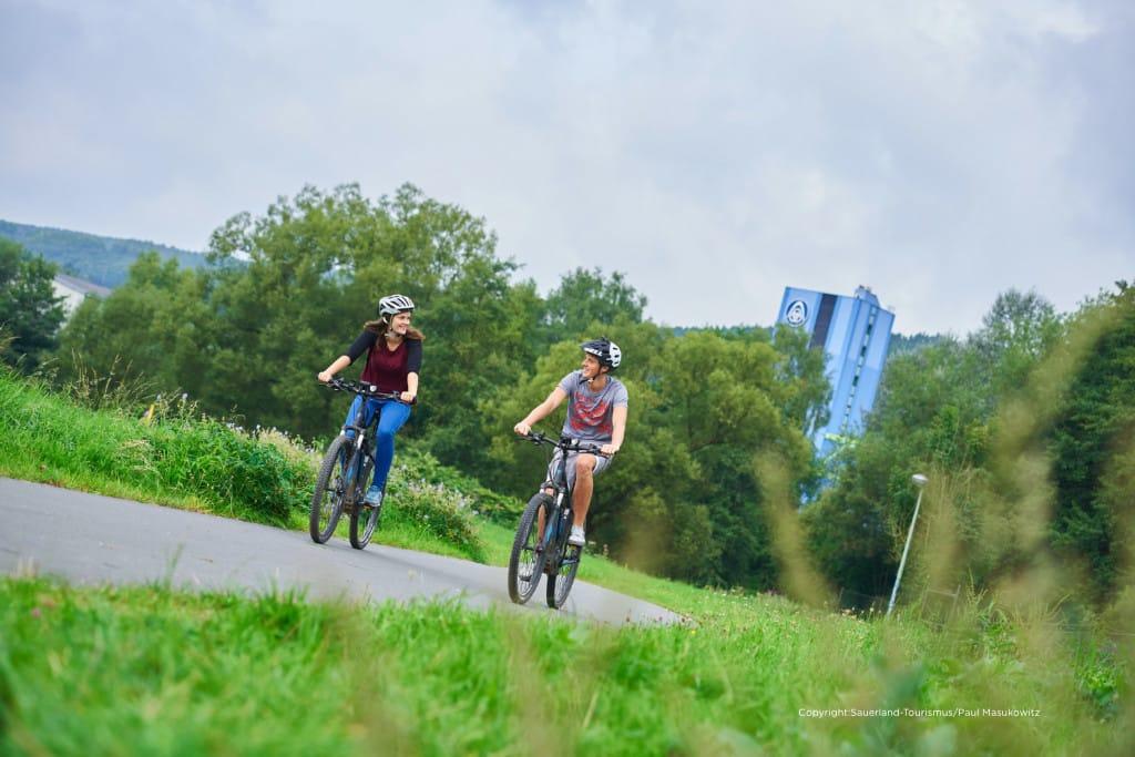 Zwei Radfahrer auf dem SauerlandRadring inmitten grüner Natur mit Industriegebäude im Hintergrund. Für Tourenradler ist der SauerlandRadring als Drehschreibe des Radfahrens im Sauerland der ideale Einstieg, um die Region mit dem Rad zu entdecken. Wo einst Dampfloks über die Gleise schnauften kommt heute kein Radler mehr aus der Puste. Größtenteils auf alten Bahntrassen angelegt, verbindet er die Orte Finnentrop, Eslohe, Schmallenberg und Lennestadt auf insgesamt 84 Kilometern und verspricht dabei Radfahrspaß mitten in der Natur. Mehr Infos unter: www.sauerlandradring.de