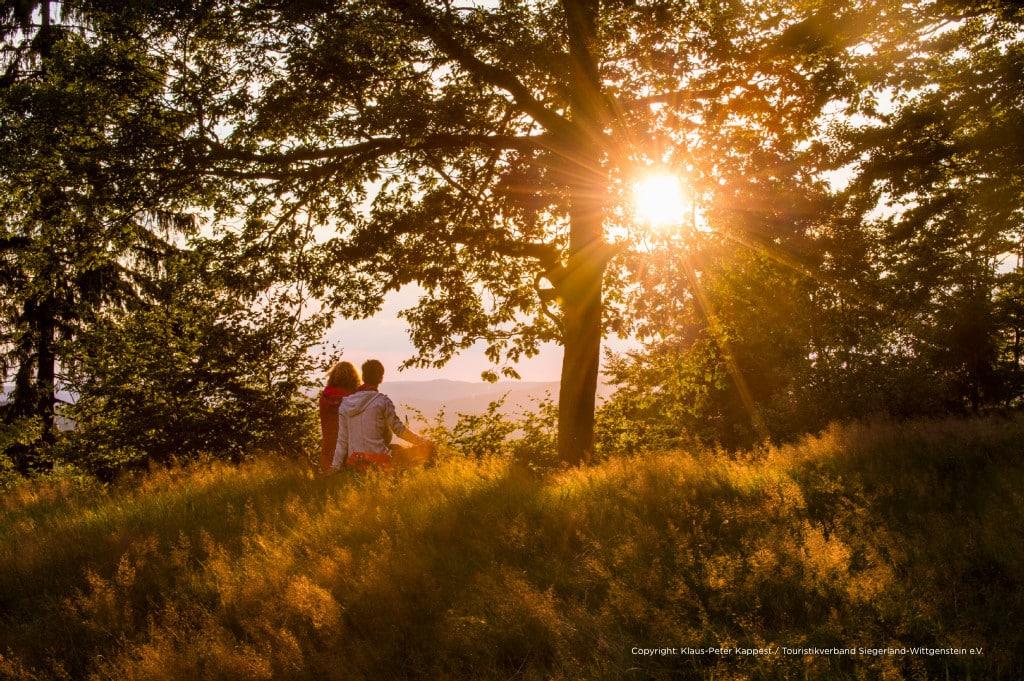 """An der """"schönen Aussicht"""" oberhalb von Sohlbach sitzen zwei Frauen auf einem Baumstamm und schauen in den Sonnenuntergang hinein."""